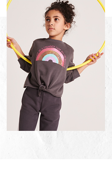 Girl with hula hoop wearing grey sports top and bottoms