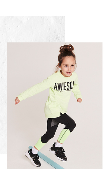 Girl jogging wearing neon green 'Awesome' slogan sports top, matching bottoms and black gym trainers
