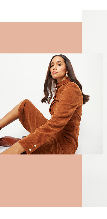 Woman sitting on the floor wearing a brown corduroy jumpsuit