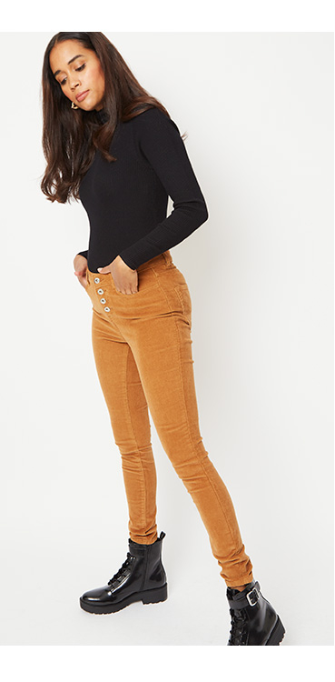 Woman wearing a black long sleeve top with mustard coloured corduroy trousers and black boots