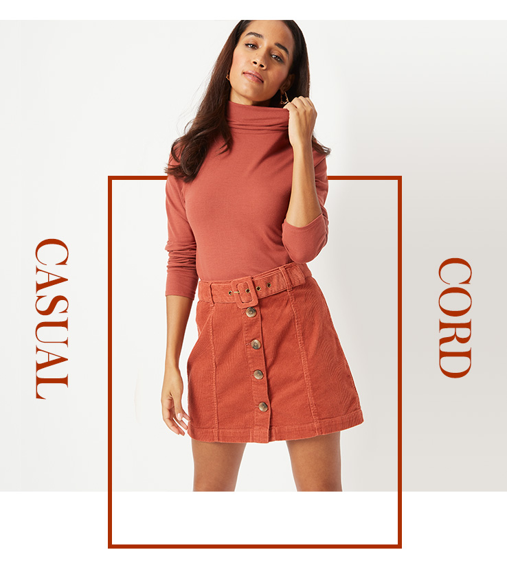 Woman wearing a salmon pink turtleneck top and matching corduroy skirt