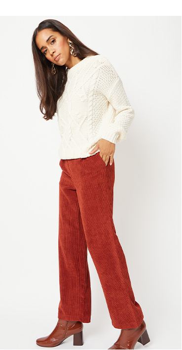 Woman wearing a cream jumper and corduroy trousers