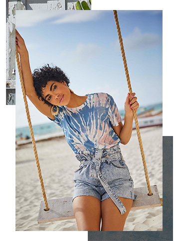 Dress up for balmy evening strolls by the beach with a tie dye T-shirt and denim shorts
