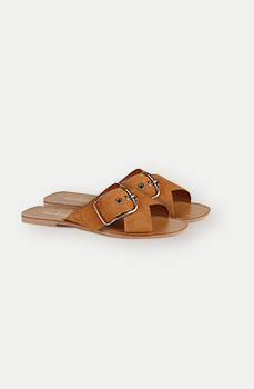 These tan suede sandals feature crossover straps and a large buckle detail