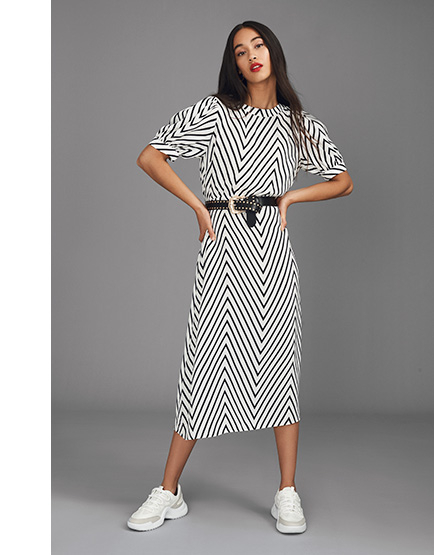 Woman wearing chevron print dress with black belt and white trainers
