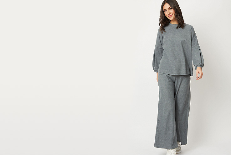Woman in grey loungewear jumper and matching loose grey loungewear trousers on a neutral background