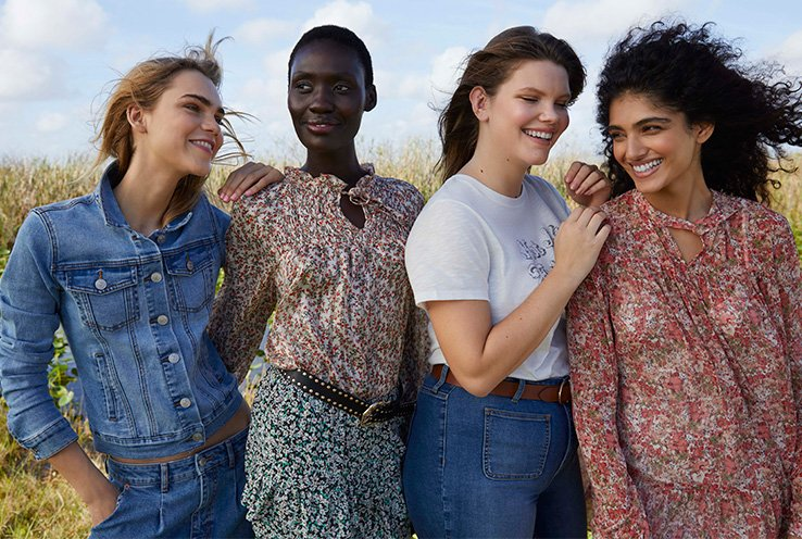 Four women in a field wearing George Pretty Western trend clothing, including a denim jacket, slogan T-shirt, floral blouse and floral dress