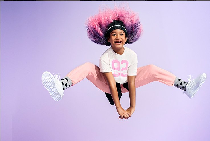 A girl jumping in the air wearing a white slogan t-shirt, pink joggers, grey spotted socks and white trainers.