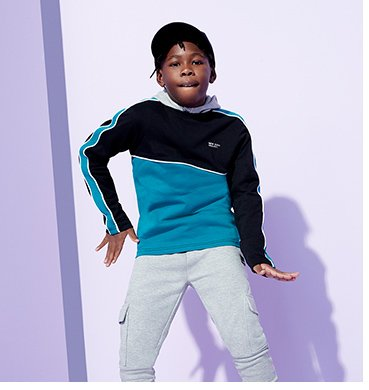 A dancing boy wearing a blue and black jumper with grey joggers.