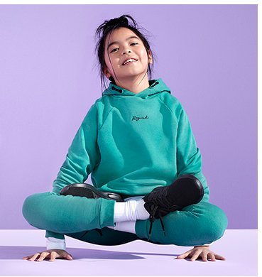 A girl doing a yoga pose wearing a teal hoodie and joggers outfit with white socks and black trainers.