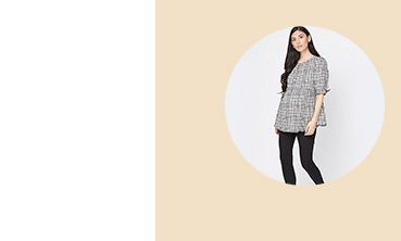Woman with long dark hair poses wearing maternity grey checkered blouse with maternity black over the bump ponte leggings.