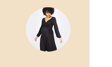 Woman with black curly hair poses wearing maternity black v-neck midi nursing dress.