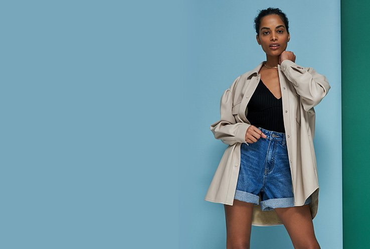 Woman poses in front of blue and green background wearing black v-neck cami, beige oversized shirt and turn-up denim shorts.