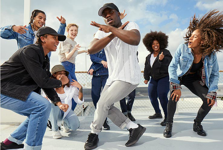 A group of men and women in various dance poses wearing George denim and other clothing