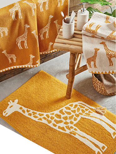 Ochre towels and a matching rug in a bathroom, all designed with giraffes