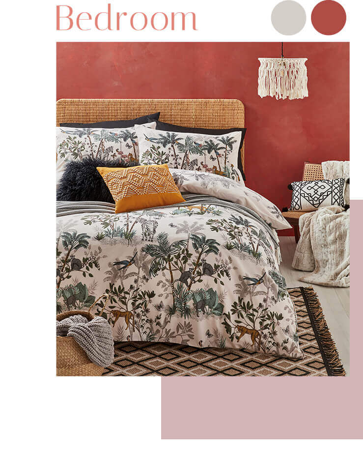 Double bed with jungle print bedding, a grey knitted throw, a black faux fur cushion and an ochre patterned cushion