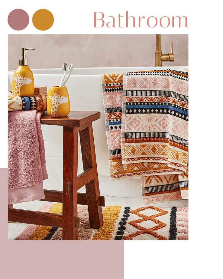 A bathroom with tribal patterned towels over a bath, a matching rug and a table with giraffe tumbler and dispenser
