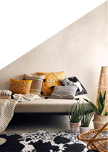 Sofa with an assortment of cushions, a striped throw, a cow print rug and artificial plants in pots