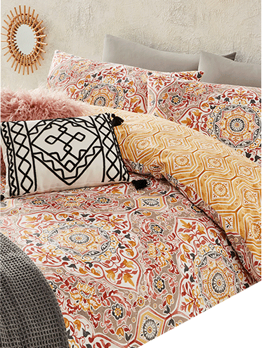 Double bed with tile print bedding, a pink faux fur cushion and a monochrome patterned cushion