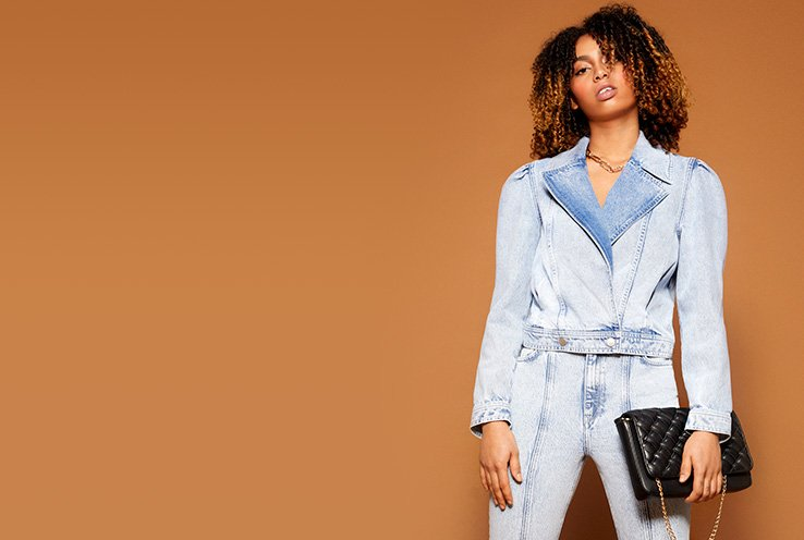 Phoenix Brown poses wearing light wash cropped denim blazer and light wash jeans holding black quilted bag.