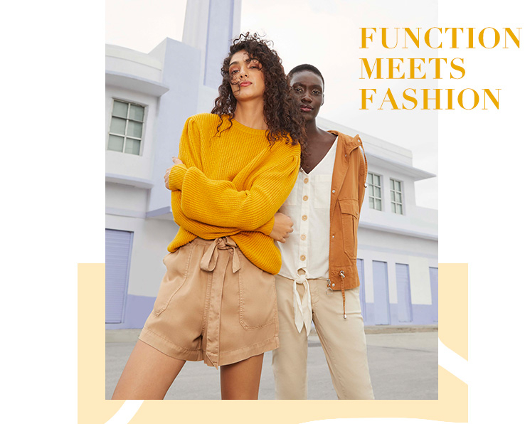 Woman wearing Mustard Yellow Pleated Sleeve and Beige Tie Waist Shorts standing with woman wearing Tan Lightweight Short Parka, Cream Tie Front Linen Sleeveless Top and Stone Relaxed Chinos