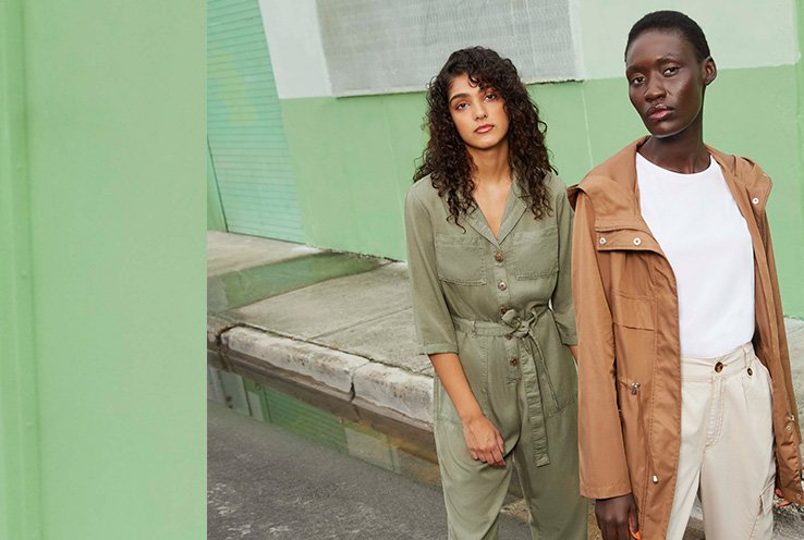 Woman wearing Khaki Button Front Boiler Suit standing with woman wearing Tan Lightweight Hooded Parka, White Crew T-Shirt and Sand Button Cargo Trousers