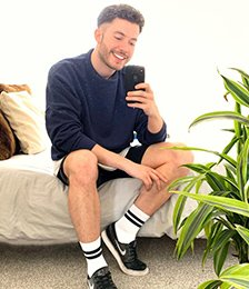 Man wearing a navy jumper and shorts taking a selfie