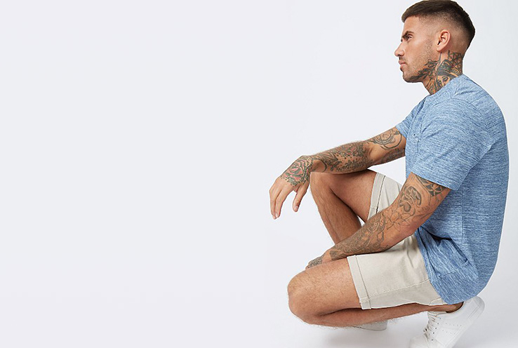 Man with tattoos wearing a light blue shirt and white chino shorts