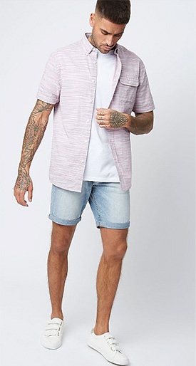Man with tattoos wearing a light purple over shirt with a white-shirt and light denim shorts