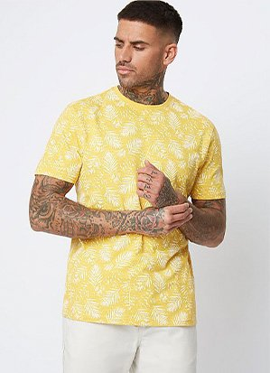 Man with tattoos wearing a yellow patterned t-shirt