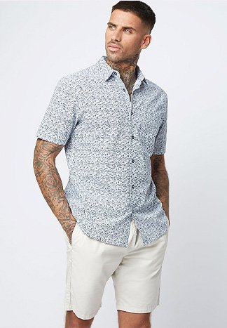 Man with tattoos wearing a patterned light blue shirt and white chino shorts