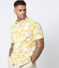 Man with tattoos wearing a yellow and white patterned shirt