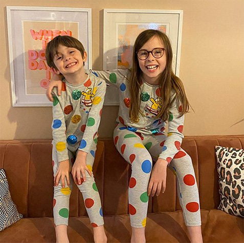 Boy and girl in matching Pudsey pyjamas in grey and multi coloured spots