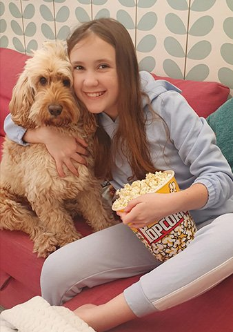 Girl hugging her dog eating popcorn wearing a grey one piece