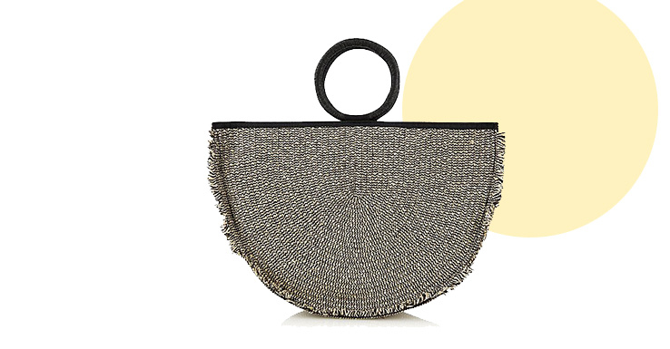 This woven bag features a small round handle and frilly trim