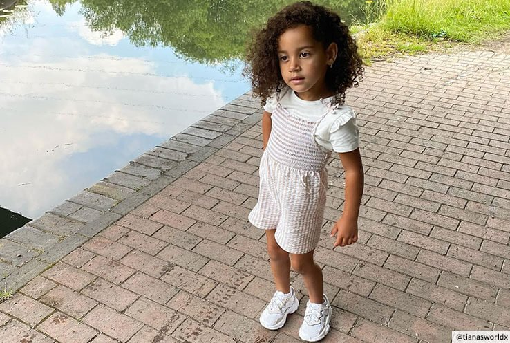 A young girl on a brick path wearing a white dress, white t-shirt and white trainers.
