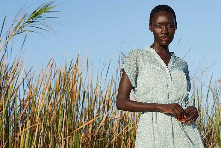 Woman standing in a crop field wearing a mint green belted midi crew neck dress