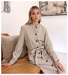 Woman sitting on a leather sofa wearing a beige button front utility dress