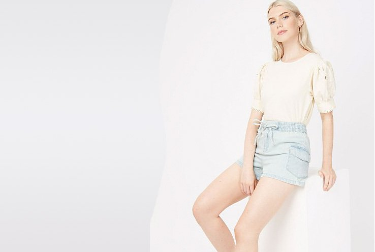 A woman sitting on a white box wearing a cream blouse with puff sleeves and lightwash denim shorts