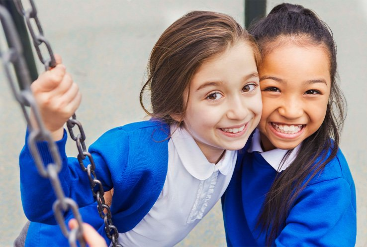 Two school girls standing together and smiling wide, both wearing white polo shirts and blue cardigans and jumpers