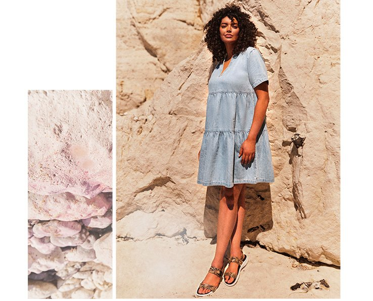 Woman in front of a large rock wall wearing a light wash denim v-neck tired smock dress with strappy sandals
