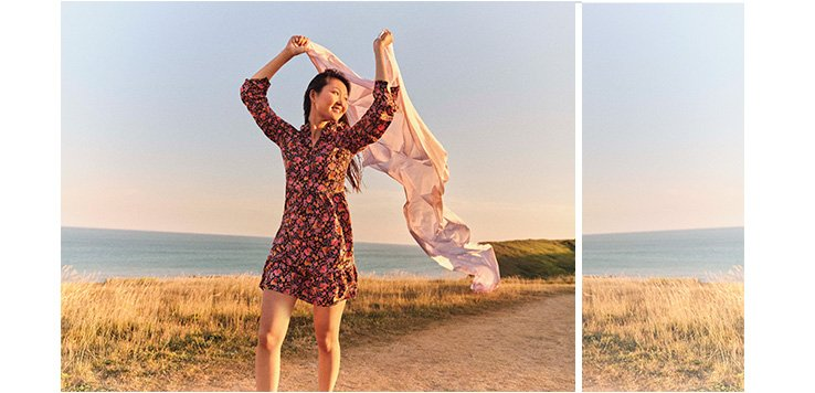 Woman on a beach path wearing a floral print ruffle hem tea dress and holding flowing fabric