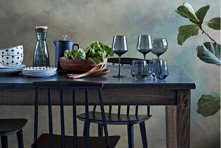 A wooden dining table topped with blue glassware, white patterned crockery, a wooden salad bowl and blue jugs