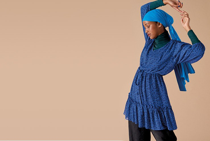 A woman with her hands over her head wearing a blue tiered dress, black trousers and a blue headscarf