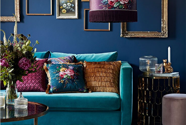 A teal velour sofa topped with a selection of embroidered, fringe and velour cushions and a coffee table topped with bright flowers in front of a dark blue wall with a selection of ornate frames