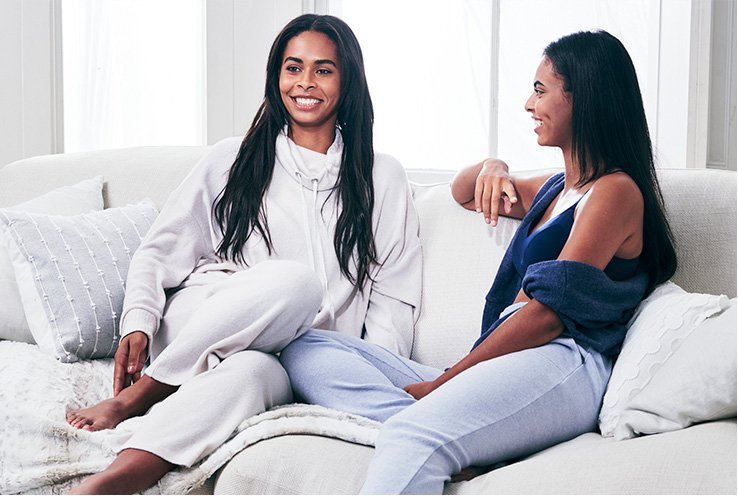 Two women sitting on a light grey sofa in loungewear outfits