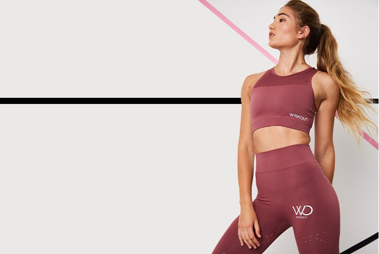 A woman looking to the side in a maroon WRKOUT sports bra and leggings set