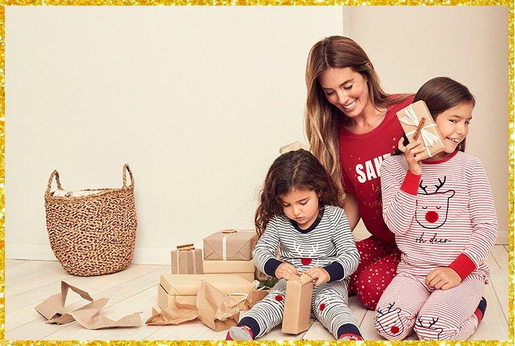 Woman wearing red Santa slogan pyjamas sitting with two girls wearing striped reindeer pyjamas opening gifts next to a wicker storage basket.