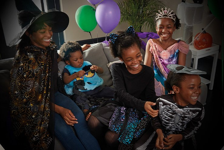 Woman and four children wearing Halloween Costumes laugh together in decorated room with baloons and pumpkin in the background.
