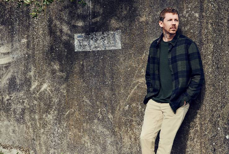 Professor Green leans against wall wearing cream trousers, green t-shirt and green and black checkered shirt.